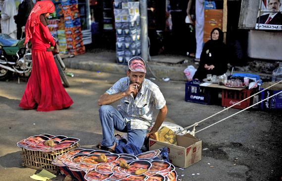 Un comerciante ambulante vende caretas del depuesto presidente egipcio Mursi en El Cairo. / AFP